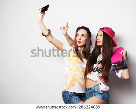 Sporty girlfriends standing having fun together. Beautiful women making selfie.Positive  emotion. White background. - stock photo
