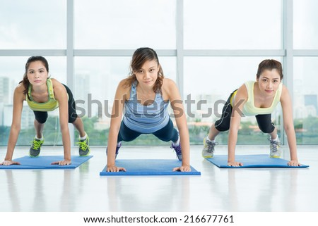 Sporty girls doing press-ups during the training in the sports club - stock photo