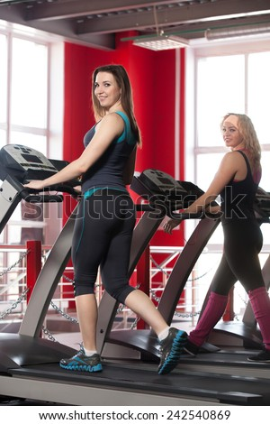 Sporty girls walking on cardio trainer, treadmill in gym - stock photo