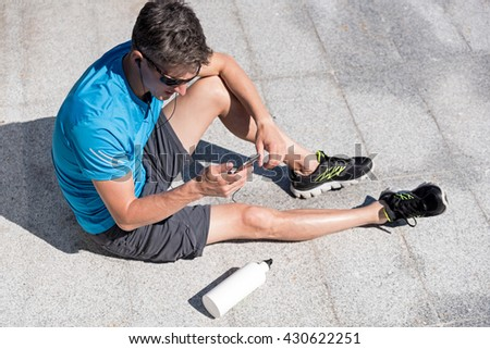 Sporty guy listening to music while training - stock photo