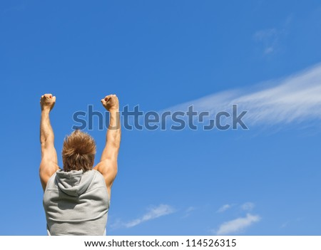 Sporty guy with his arms raised in joy, on blue sky background. - stock photo