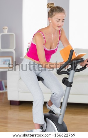 Sporty happy blonde training on exercise bike reading a book in bright living room - stock photo