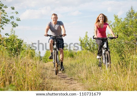 Sporty  happy couple biking in the summer park - stock photo