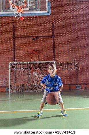 Sporty little boy playing basketball on an indoor court standing below the goal bouncing the ball and smiling at the camera - stock photo