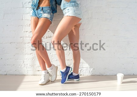 sporty long sexy legs of two beautiful women jeans shorts urban casual street style fashion sunny day standing near to the wall. - stock photo