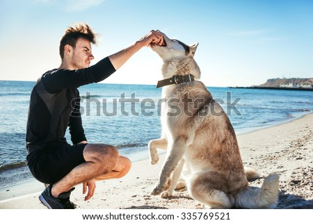 sporty male playing with two husky dogs on beach - stock photo