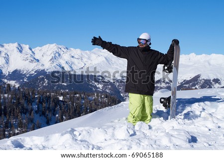 Sporty male snowboarder pointing hand in his right