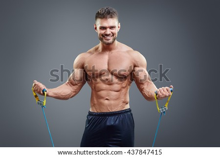 Sporty man exercising with rubber expander over grey background. Smiling strong athlete stretching muscles.