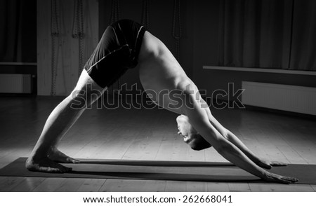 sporty  man practicing yoga in the sports hall - stock photo