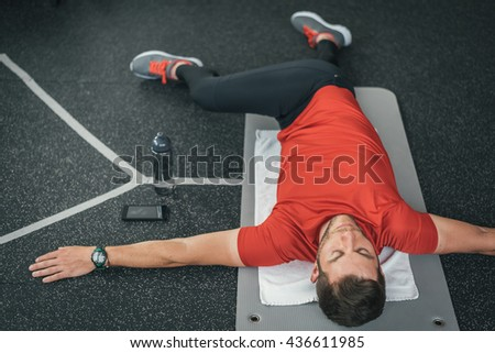 Sporty man stretching back before gym workout. Fitness strong male athlete on floor mat and towel warming up with bottle and cellphone. - stock photo