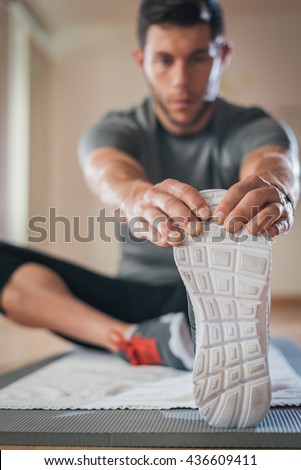 Sporty man stretching leg before gym workout. Fitness strong male athlete on floor mat and towel warming up indoor.