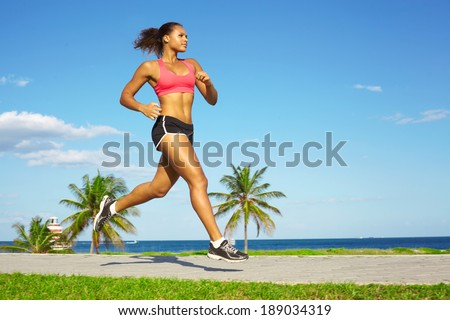 Sporty mixed race woman jogging. Color image, copy space, african american ethnicity female running with green grass and blue sky. - stock photo