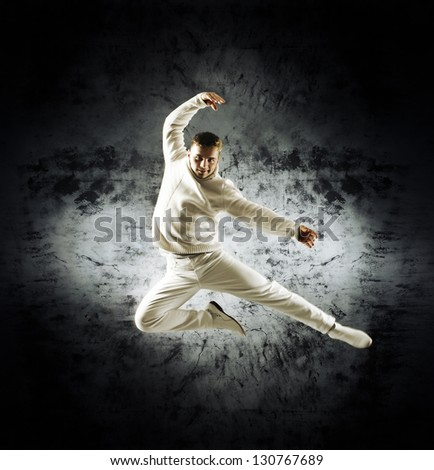Sporty modern dancer over the dramatic background in sepia style - stock photo