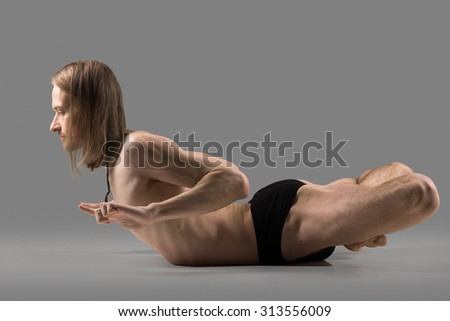 Sporty muscular young yogi man with long hair doing backbend posture, studio shot on dark background, side view, full length