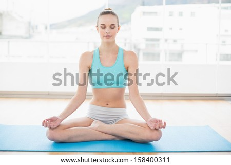 Sporty peaceful woman sitting cross-legged on exercise mat in bright room