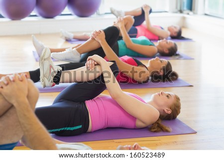 Sporty people doing the supine wind release posture on mats at yoga class in fitness studio - stock photo