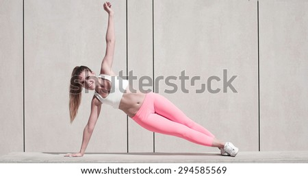 Sporty Pretty Young Woman Doing a Side Plank Exercise with One Arm Raised on a White Platform - stock photo