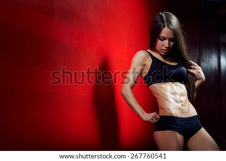 Sporty sexy girl with great abdominal muscles in black sportswear on a red wall. Fitness girl posing in the gym. Brunette in the gym. Fitness sexy girl in underwear.