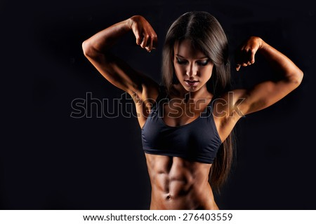 Sporty sexy girl with great abdominal muscles in black sportswear. Tanned young sexy athletic girl. A great sport female body. The girl athlete demonstrates chiseled biceps. Miss fitness bikini  - stock photo