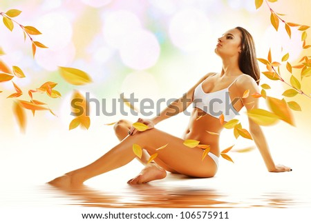 Sporty sexy woman siting on the floor with yellow leaves - stock photo