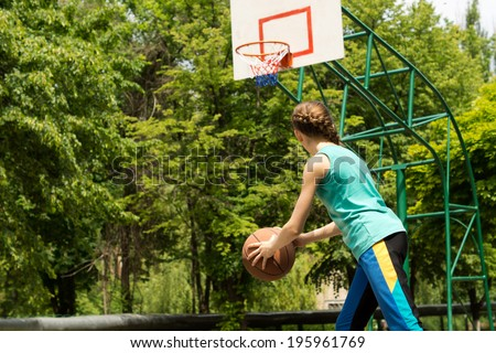 Sporty slender teenage girl playing basketball holding the ball in her hands as she moves forwards eyeing the goalpost on an outdoor court against green trees