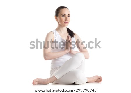 Sporty smiling beautiful young woman sitting in Gomukhasana, Cowface pose (yin yoga Shoelace posture) with hands in Namaste, studio full length shot on white background, three-quarters view, isolated - stock photo