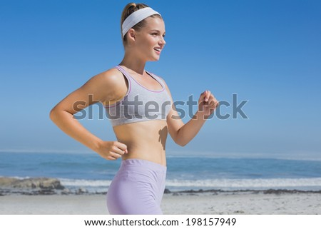 Sporty smiling blonde jogging on the beach on a sunny day