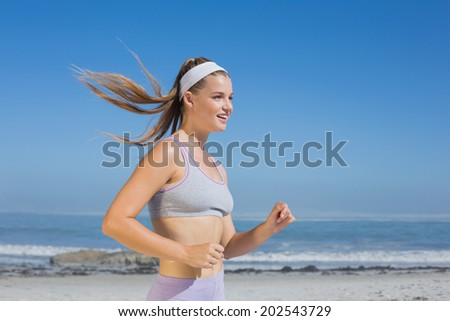 Sporty smiling blonde jogging on the beach on a sunny day - stock photo