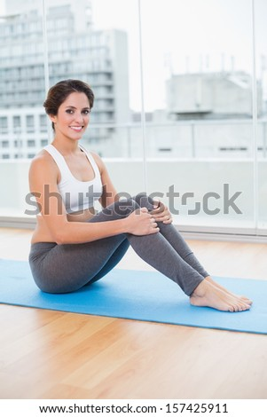 Sporty smiling brunette sitting on exercise mat in bright room