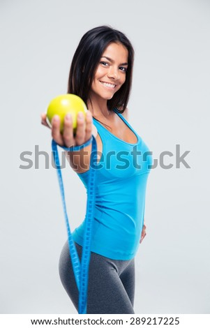 Sporty smiling woman holding apple and measuring tape over gray background - stock photo