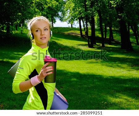 Sporty smiling woman in a park with bottle  - stock photo