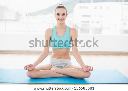 Sporty smiling woman sitting cross-legged on exercise mat in bright room