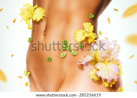 sporty torso of woman in yellow flowers with flying petals - stock photo