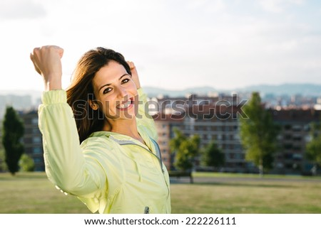 Sporty urban woman celebrating sport and fitness lifestyle success. Happy female athlete raising arms after achieving exercising goals in city park. - stock photo