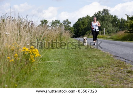 Sporty woman and dog jogging along a road in summertime - stock photo