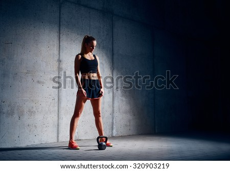 Sporty woman before kettlebell exercise - stock photo