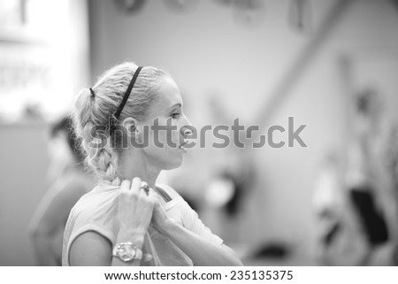 Sporty woman close up profile in the fitness center, feeling tired; monochrome - stock photo
