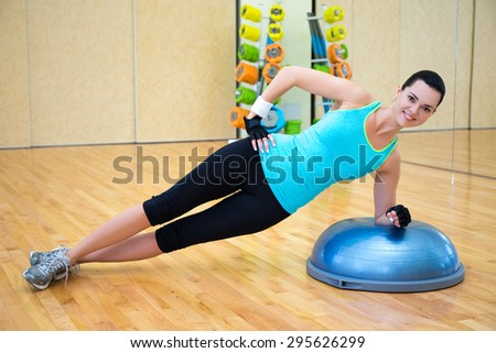 sporty woman doing exercises for abdominal muscles on bosu ball in gym - stock photo