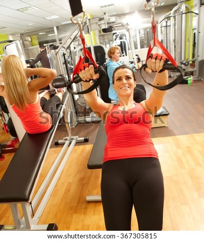Sporty woman doing TRX exercises in gym. - stock photo