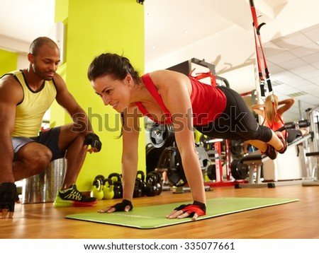 Sporty woman doing TRX suspension training with personal trainer in gym. - stock photo