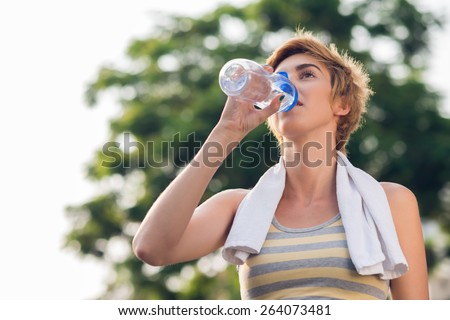 Sporty woman drinking water after training - stock photo
