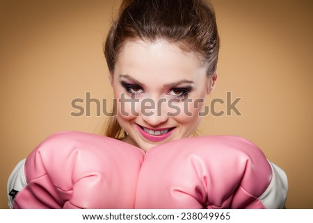 Sporty woman female boxer model wearing big fun pink gloves playing sports boxing studio shot, brown background - stock photo