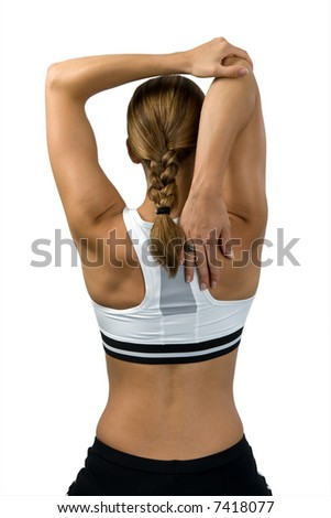 Sporty woman from behind. She stretches her muscles - triceps and shoulder.