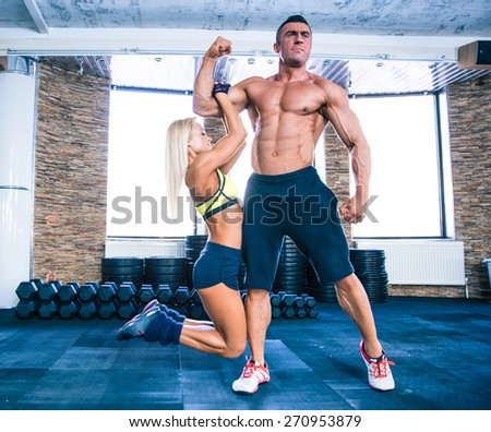 Sporty woman hanging on a hand of muscular man at gym - stock photo
