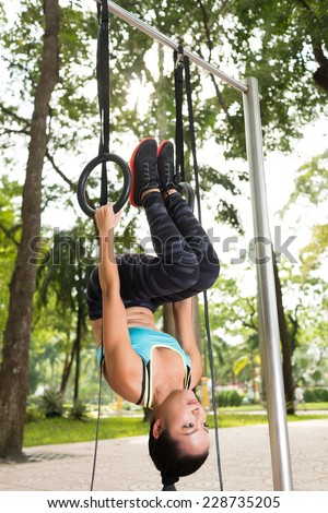Sporty woman hanging on gymnastic rings upside down  - stock photo