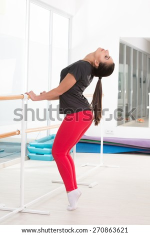 Sporty woman in gym in yellow t-shirt and black jogging bottoms - stock photo