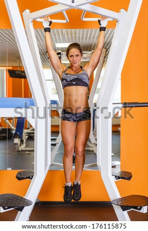 Sporty woman is doing exercises on power training apparatus in the gym. Pulling up on the horizontal bar. - stock photo