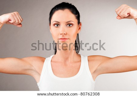 sporty woman is showing her strong hands on grey background - stock photo