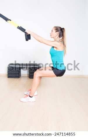 Sporty woman makes suspension training - stock photo