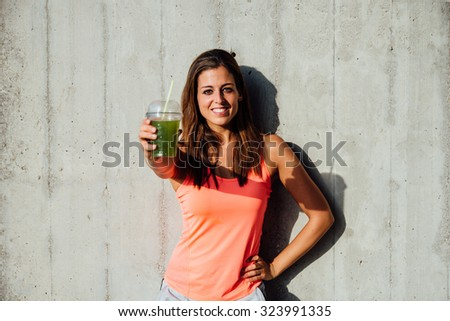 Sporty woman offering detox green smoothie. Happy sportswoman showing healthy fruit and vegetables drink. Fitness lifestyle and nutrition concept. - stock photo